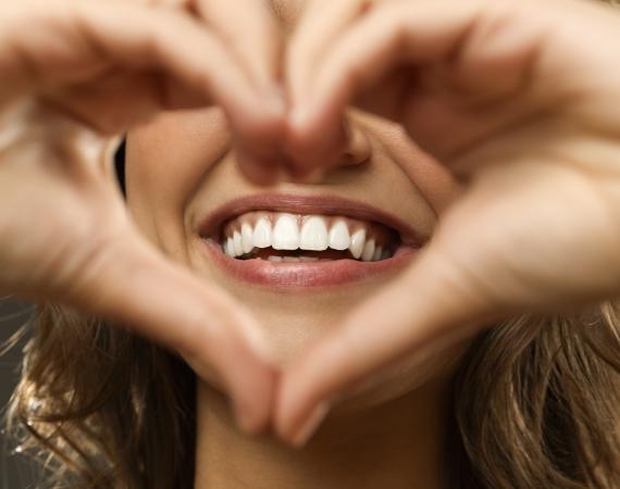 uśmiechnięta kobieta składająca dłonie wkształt serca
